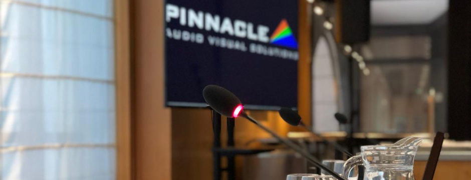 Delegate interpretation microphones on a table top with logo of our partner Pinnacle AV behind