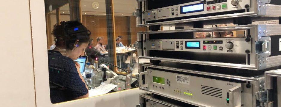 sound mixing gear beside interpreter in booth